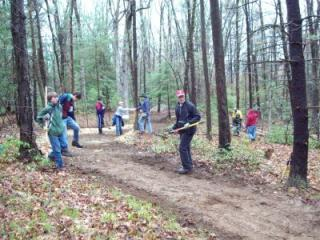 A group of volunteers does work on the Pond Loop trail